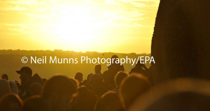 Revelers enjoy the sunrise on the longest day of the year, the summer solstice at Stonehenge in Wiltshire uk